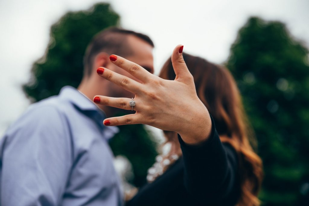 Woman showing off her diamond ring while kissing her boyfriend