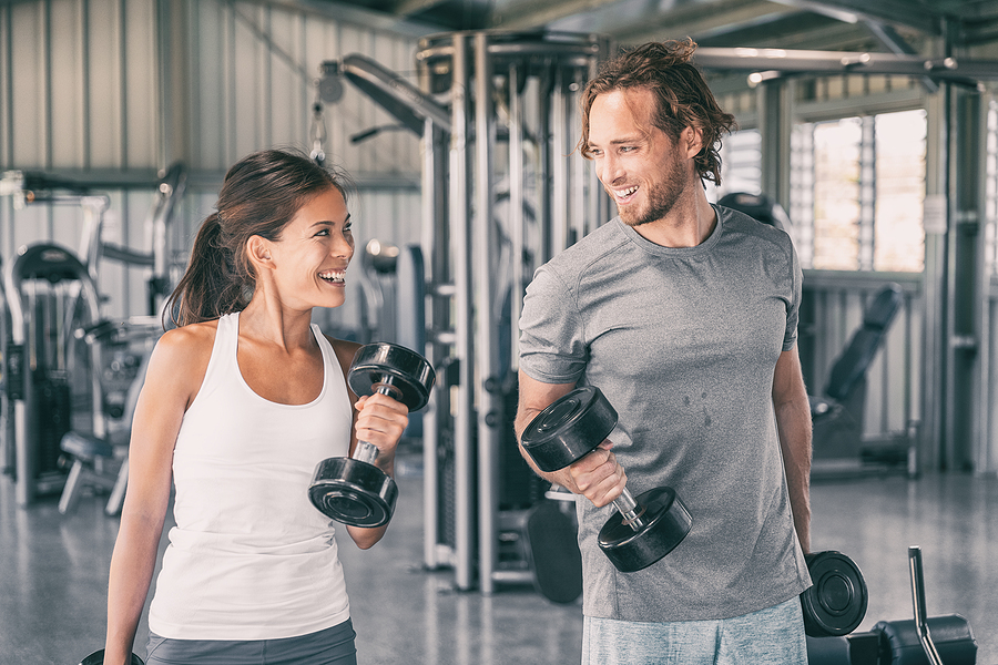 Man and a woman using adjustable dumbbell barbell set